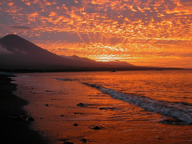 fiery sunset behind Mount Agung volcano at Amed Beach, Bali, Indonesia