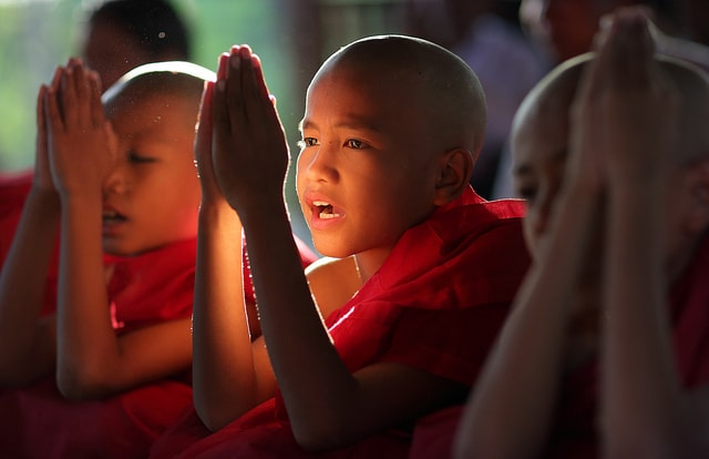 Buddhist novice monk child in red robe in Burma (Myanmar)