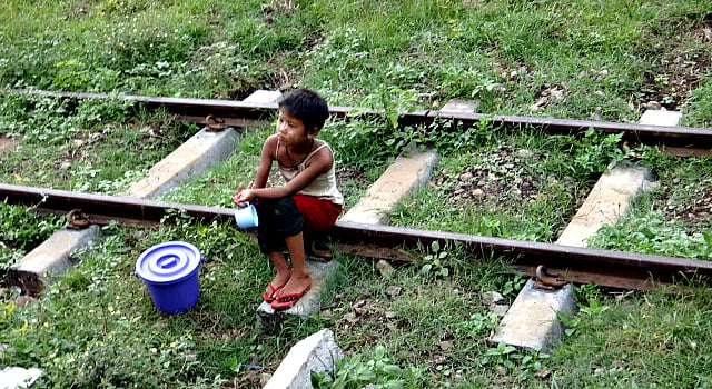 child in Shan State, Myanmar sitting on the traintracks